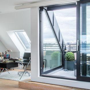 Idéer för ett stort modernt arbetsrum, med vita väggar, ljust trägolv och ett fristående skrivbord