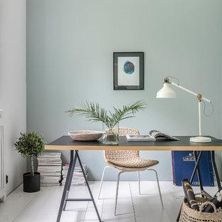 Пример оригинального дизайна: маленький кабинет в скандинавском стиле с зелеными стенами, деревянным полом, отдельно стоящим рабочим столом и белым полом