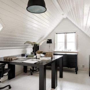 Inredning av ett minimalistiskt arbetsrum, med vita väggar, målat trägolv, ett fristående skrivbord och vitt golv
