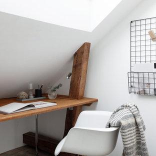 Inspiration för ett litet skandinaviskt hemmabibliotek, med vita väggar, mellanmörkt trägolv, ett inbyggt skrivbord och brunt golv
