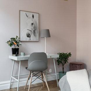Immagine di un piccolo studio scandinavo con pareti rosa, parquet chiaro, scrivania autoportante e pavimento beige