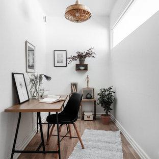 Idéer för minimalistiska hemmabibliotek, med vita väggar, mellanmörkt trägolv, ett fristående skrivbord och beiget golv