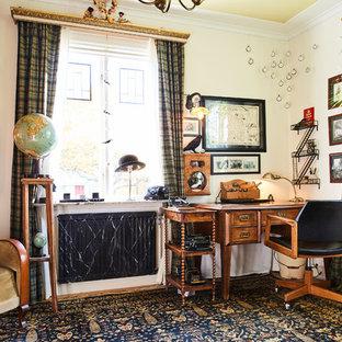 Eklektisk inredning av ett hemmabibliotek, med vita väggar, ljust trägolv och ett fristående skrivbord
