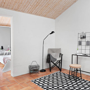 Contemporary home office and library in Malmo with white walls, terracotta flooring and a freestanding desk.