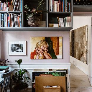 Bild på ett eklektiskt hemmabibliotek, med rosa väggar, ljust trägolv, ett fristående skrivbord och beiget golv