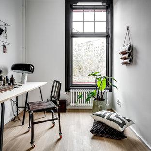 Exempel på ett mellanstort industriellt arbetsrum, med vita väggar, ljust trägolv, ett fristående skrivbord och brunt golv