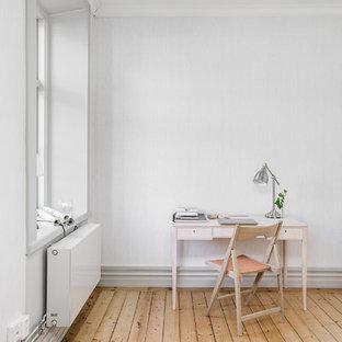 Bild på ett skandinaviskt arbetsrum, med vita väggar, ljust trägolv, ett fristående skrivbord och beiget golv