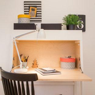 На фото: с невысоким бюджетом маленькие рабочие места в скандинавском стиле с белыми стенами, отдельно стоящим рабочим столом и паркетным полом среднего тона без камина