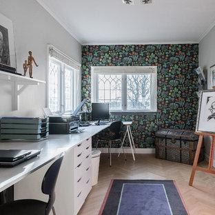 Modern inredning av ett mellanstort hemmabibliotek, med flerfärgade väggar, ljust trägolv och ett inbyggt skrivbord