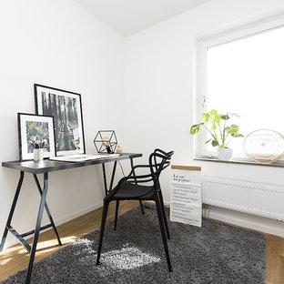 Inspiration för nordiska arbetsrum, med vita väggar, ljust trägolv, ett fristående skrivbord och brunt golv