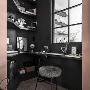 Стильный дизайн: домашняя мастерская в скандинавском стиле с черными стенами, ковровым покрытием, встроенным рабочим столом и серым полом - последний тренд