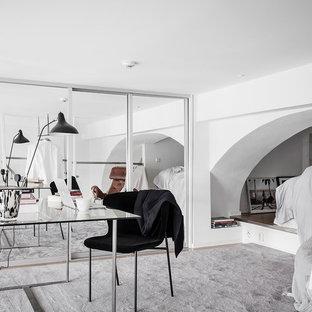 Foto på ett skandinaviskt arbetsrum, med vita väggar och ett fristående skrivbord