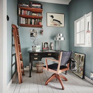 Minimalistisk inredning av ett mellanstort hemmabibliotek, med blå väggar, målat trägolv och ett fristående skrivbord