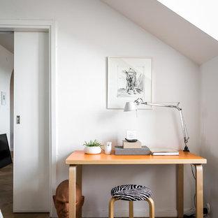 Inspiration för mellanstora minimalistiska hemmabibliotek, med vita väggar, ett fristående skrivbord och ljust trägolv