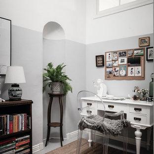 Idéer för ett minimalistiskt hemmabibliotek, med grå väggar, målat trägolv, ett fristående skrivbord och grått golv