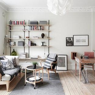 Стильный дизайн: рабочее место среднего размера в скандинавском стиле с белыми стенами, светлым паркетным полом и отдельно стоящим рабочим столом без камина - последний тренд