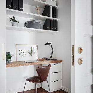 Réalisation d'un bureau nordique avec un mur blanc, un sol en bois foncé, un bureau intégré et un sol marron.