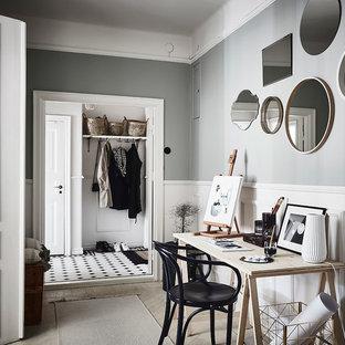 На фото: рабочее место среднего размера в скандинавском стиле с серыми стенами, светлым паркетным полом и отдельно стоящим рабочим столом без камина с