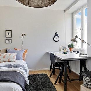 Nordisk inredning av ett litet arbetsrum, med ett fristående skrivbord, vita väggar, mellanmörkt trägolv och brunt golv