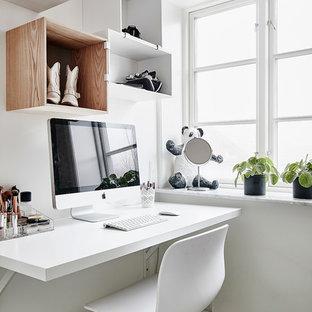 Idée de décoration pour un grand bureau atelier nordique avec un mur blanc, un sol en bois clair, un bureau intégré et un sol marron.