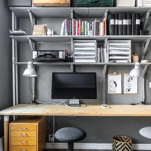 Inspiration för små minimalistiska hemmabibliotek, med grå väggar, mellanmörkt trägolv, ett fristående skrivbord och grått golv