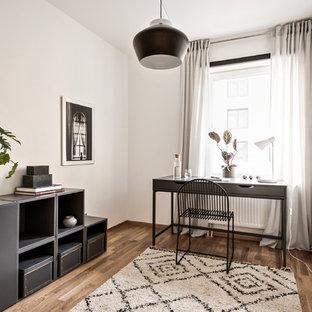 Inredning av ett skandinaviskt hemmabibliotek, med vita väggar, mellanmörkt trägolv, ett fristående skrivbord och brunt golv