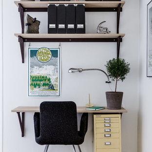 Inspiration för ett litet minimalistiskt arbetsrum, med vita väggar, ljust trägolv och ett inbyggt skrivbord