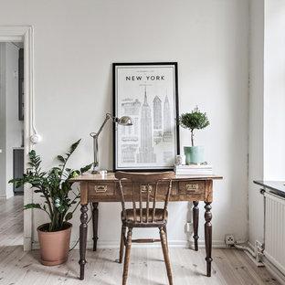 Idéer för ett litet minimalistiskt hemmabibliotek, med vita väggar, ljust trägolv, ett fristående skrivbord och beiget golv