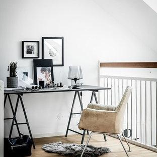 Idéer för ett skandinaviskt hemmabibliotek, med vita väggar, ljust trägolv, ett fristående skrivbord och beiget golv