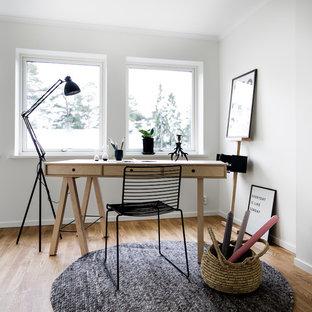 Exempel på ett skandinaviskt arbetsrum, med vita väggar, mellanmörkt trägolv, ett fristående skrivbord och brunt golv