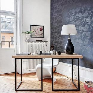 Inspiration för ett mellanstort minimalistiskt hemmabibliotek, med svarta väggar, mellanmörkt trägolv och ett fristående skrivbord