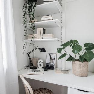 Nordisk inredning av ett arbetsrum, med vita väggar, mörkt trägolv, ett inbyggt skrivbord och brunt golv