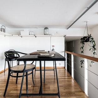 Bild på ett minimalistiskt arbetsrum, med vita väggar, mellanmörkt trägolv, ett fristående skrivbord och brunt golv