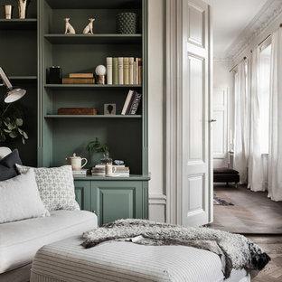 На фото: кабинет в скандинавском стиле с зелеными стенами и темным паркетным полом с