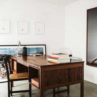 Exempel på ett minimalistiskt hemmabibliotek, med vita väggar, betonggolv, ett fristående skrivbord och grått golv