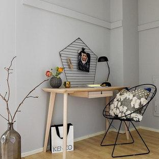 Inredning av ett minimalistiskt mellanstort arbetsrum, med grå väggar, ljust trägolv, ett fristående skrivbord och gult golv