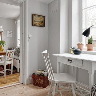 Bild på ett mellanstort skandinaviskt hemmabibliotek, med grå väggar, ljust trägolv och ett fristående skrivbord