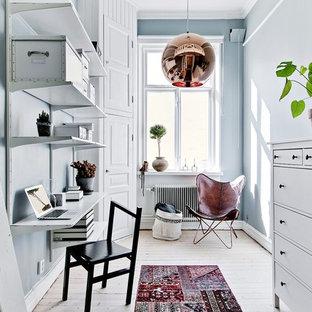 Minimalistisk inredning av ett litet hemmabibliotek, med blå väggar, ljust trägolv, beiget golv och ett inbyggt skrivbord