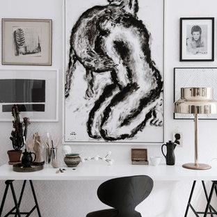 Inredning av ett minimalistiskt stort hobbyrum, med vita väggar, ljust trägolv och ett fristående skrivbord