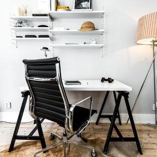 Exempel på ett nordiskt arbetsrum, med vita väggar, ljust trägolv, ett fristående skrivbord och beiget golv