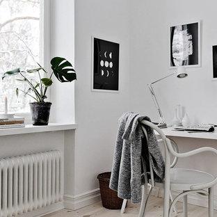 Inspiration för ett mellanstort nordiskt hemmabibliotek, med vita väggar, ljust trägolv och ett fristående skrivbord