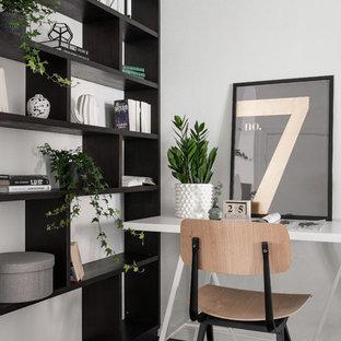 Minimalistisk inredning av ett hemmabibliotek, med vita väggar, mörkt trägolv, ett fristående skrivbord och svart golv