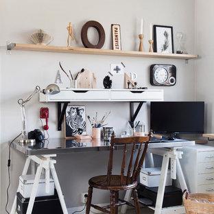 Foto på ett mellanstort industriellt arbetsrum, med grå väggar, målat trägolv och ett fristående skrivbord