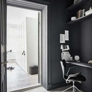 Immagine di uno studio nordico di medie dimensioni con pareti nere, pavimento in legno verniciato, nessun camino e scrivania autoportante
