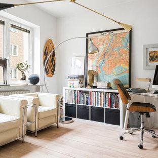 Exempel på ett eklektiskt arbetsrum, med vita väggar, ljust trägolv, ett fristående skrivbord och beiget golv