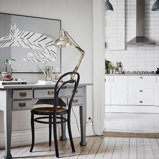 Nordisk inredning av ett arbetsrum, med grå väggar, målat trägolv, ett fristående skrivbord och vitt golv