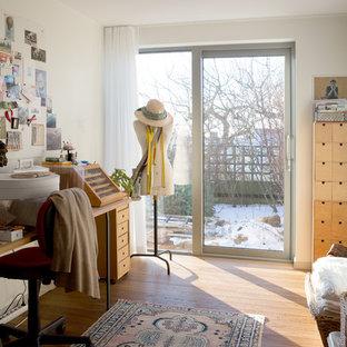 Inspiration för ett minimalistiskt hobbyrum, med vita väggar, ljust trägolv, ett fristående skrivbord och beiget golv