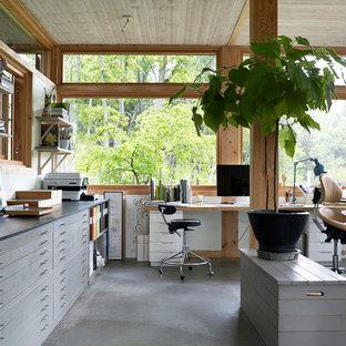 ストックホルムの大きいアジアンスタイルのおしゃれなホームオフィス・書斎 (コンクリートの床、暖炉なし、自立型机、グレーの床) の写真