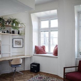 Inspiration för ett skandinaviskt hemmabibliotek, med vita väggar, mellanmörkt trägolv och ett inbyggt skrivbord