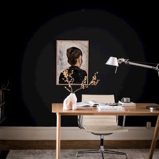 Inspiration för skandinaviska arbetsrum, med svarta väggar, mörkt trägolv, ett fristående skrivbord och brunt golv